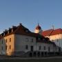 Widok na budynek dawnego klasztoru dominikanów. Za nim oświetlone zachodzącym słońcem ściany kościoła.