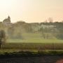 Wiosenny widok na zespół klasztorny dominikanów i cerkiew przez snujący się o zachodzie dym.