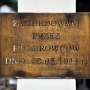 Tabliczka na krzyżu upamiętniającym pomordowanych mieszkańców Jamin przez hitlerowców w 1944 roku.
