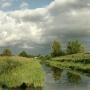 Na lewo soczyste łąki, centrum Supraśl wody toczy a na prawo zdeptana Góra Zamkowa. Nad ziemią letnie chmury wiatr przegania.
