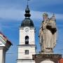 Figura św. Romualda z Camaldoli założyciela zakonu Kamedułów we Włoszech. W tle wieża zegarowa.